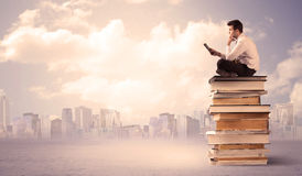 Businessman with laptop sitting on books. A serious student with laptop tablet in elegant suit sitting on a stack of books in front of cityscape with clouds Royalty Free Stock Image