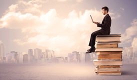 Businessman with laptop sitting on books Royalty Free Stock Images