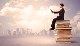 Businessman with laptop sitting on books Stock Photography