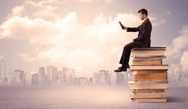 Businessman with laptop sitting on books Stock Photo