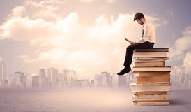 Businessman with laptop sitting on books Stock Images