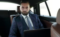 Businessman with laptop sitting in a comfortable car. Serious businessman with laptop sitting in a comfortable car Royalty Free Stock Images