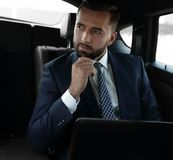 Businessman with laptop sitting in a comfortable car. Serious businessman with laptop sitting in a comfortable car Royalty Free Stock Photos