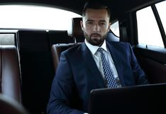 Businessman with laptop sitting in a comfortable car. Serious businessman with laptop sitting in a comfortable car Royalty Free Stock Photo
