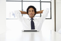 Businessman With Laptop Sitting At Desk In Office Thinking Royalty Free Stock Photo
