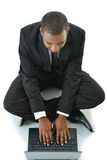 Businessman with laptop sitting on floor. Business man sitting with legs crossed working on laptop Royalty Free Stock Images