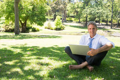 Businessman with laptop sitting on grass. Full length portrait of mature businessman with laptop sitting on grass in park Stock Image