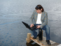 Businessman with laptop sitting on his briefcase. Near a frozen lake outdoors stock photos