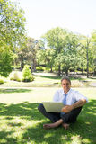 Businessman with laptop sitting in park. Full length portrait of smiling businessman with laptop sitting on grass in park Royalty Free Stock Photos
