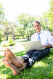 Businessman with laptop sitting in park. Portrait of mature businessman with laptop sitting on grass in park Royalty Free Stock Photo