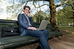 Businessman with a laptop sitting in a park Stock Image