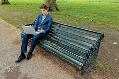 Businessman with a laptop sitting in a park Stock Photo