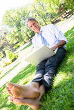 Businessman with laptop sitting on parkland. Portrait of smiling mature businessman with laptop sitting on grass in park Stock Photo