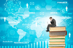 Businessman with laptop sitting on stack of books Royalty Free Stock Image