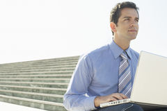 Businessman With Laptop Sitting On Staircase Against Sky Royalty Free Stock Image