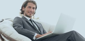 Businessman with a laptop sitting in a stylish comfortable chai. Close-up of a successful businessman with a laptop sitting in a stylish comfortable chair Royalty Free Stock Images