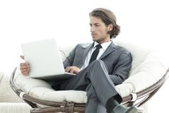 Modern businessman with a laptop sitting in a stylish comfortable chair. Businessman with a laptop sitting in a stylish comfortable chair. photo with copy space Royalty Free Stock Image