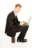 Businessman with laptop sitting on a suitcase Stock Photography