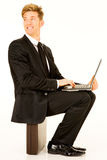 Businessman with laptop sitting on a suitcase Royalty Free Stock Photos