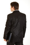 Businessman with laptop standing back to camera Royalty Free Stock Photo
