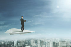 Businessman with laptop stands on paper plane Royalty Free Stock Images