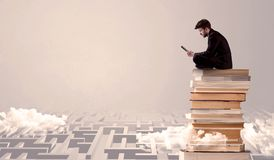Man with tablet sitting on books. A businessman with laptop tablet in elegant suit sitting on a stack of books on top of sandy labirynth background concept Royalty Free Stock Image