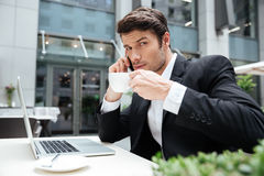 Businessman with laptop talking on mobile phone and drinking coffee Stock Photo