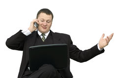 Businessman with laptop talking on phone. A young businessman with a slight smile in a dark suit with a laptop on his lap is talking on his cell phone stock photos