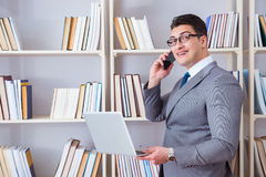 The businessman with a laptop talking on phone working in library. Businessman with a laptop talking on phone working in library Royalty Free Stock Image