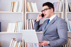 The businessman with a laptop talking on phone working in library. Businessman with a laptop talking on phone working in library Stock Photos