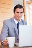 Businessman with laptop and tea Stock Photography