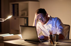 Businessman with laptop thinking at night office. Business, overwork, people, deadline and technology concept - stressed businessman in glasses with laptop Stock Image