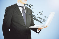 Businessman with laptop from which the words are flying Royalty Free Stock Photography
