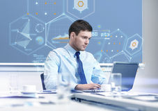 Businessman with laptop working in office Stock Photo