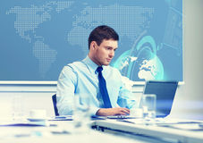 Businessman with laptop working in office Stock Images