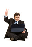 Businessman with laptops showing victory gesture Stock Image