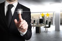 Businessman in modern office pushing virtual button two star review 3D Illustration. Businessman in large modern office pushing virtual button two star review 3D royalty free stock photo