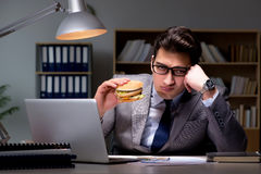 The businessman late at night eating a burger Royalty Free Stock Images