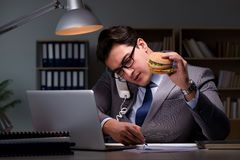 The businessman late at night eating a burger Royalty Free Stock Photography