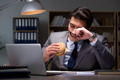 The businessman late at night eating a burger Stock Photography