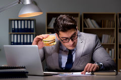 The businessman late at night eating a burger Stock Images