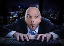 Businessman late at night in office typing on computer keyboard with funny face expression on watching online. Young businessman late at night in office typing stock images