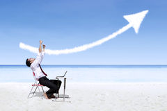 Businessman laughing in joy looking at success arrow sign at beach Stock Photo