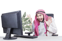 Businessman laughing with money on computer stock images