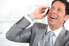Businessman laughing on the phone Stock Photo