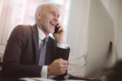 Businessman laughing on the phone stock images