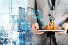 Businessman launches rocket from a tablet. concept of company startup Stock Photography