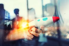 Businessman launches his startup company. Hand holding a wooden rocket. double exposure with light effects. Wooden toy on background of people silhouettes stock images