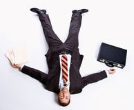 Businessman laying on floor and briefcase. Businessman laying on floor with his briefcase and paperwork Royalty Free Stock Images
