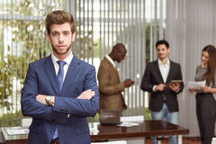 Businessman leader with arms crossed in working environment Stock Image